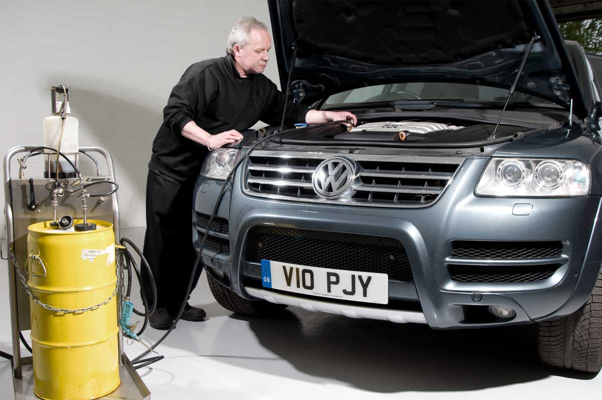 Mechanic using diagnostic equipment on Volkswagen Touareg with its bonnet up