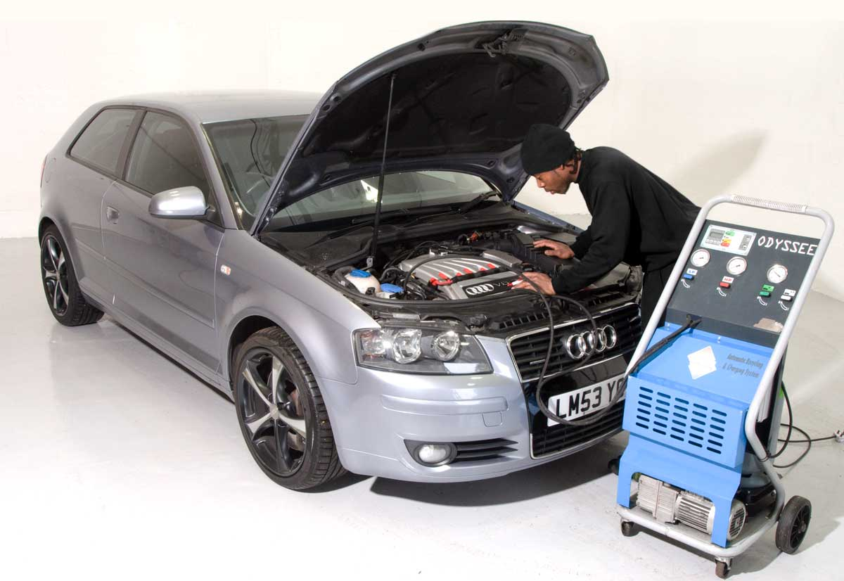 Mechanic examining an Audi with its bonnet up using diagnostic equipment