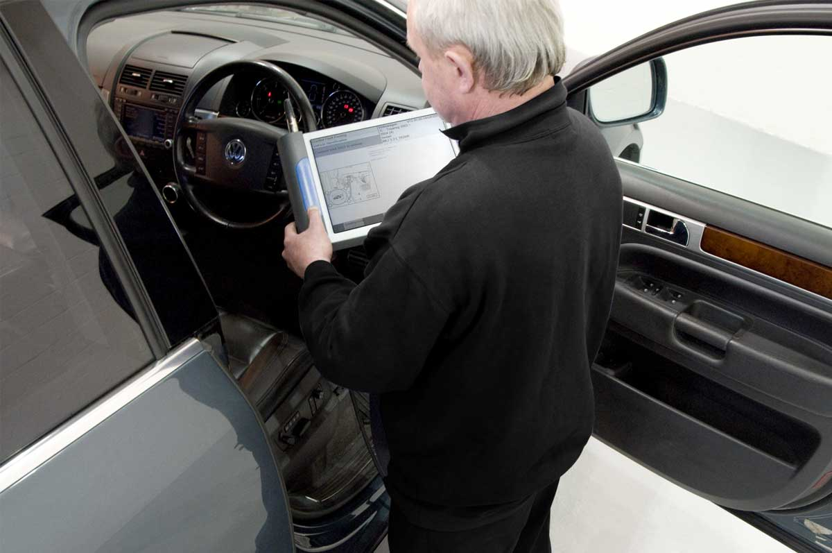 A technician using diagnostic equipment at the driver's door of a VW